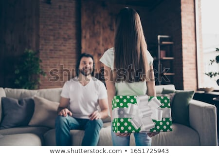 Young man holding small gift(focus on gift) Stock photo © elly_l
