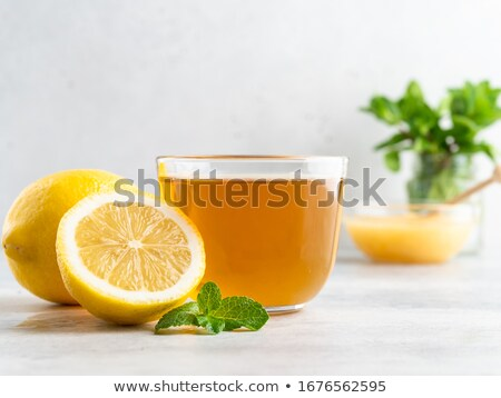 glass cup of tea with lemon and mint leaves isolated on a white stock photo © tetkoren