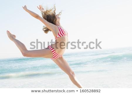Beautiful smiling woman in white bikini leaping on the beach Stock photo © wavebreak_media