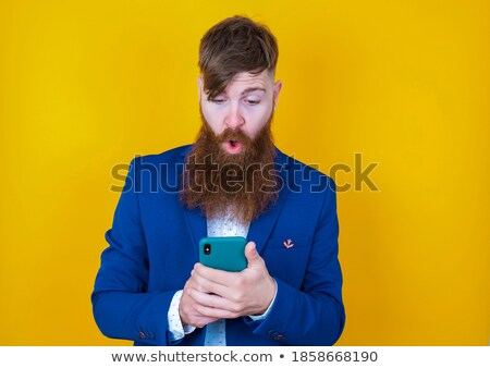 Serious businessman reading text message on smart phone against  Stock photo © traza