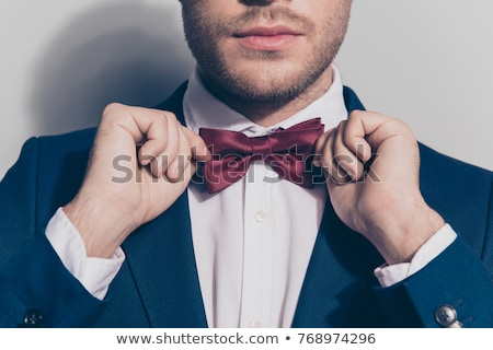 The groom in a blue shirt holding a bow tie in his hands  Stock photo © d_duda