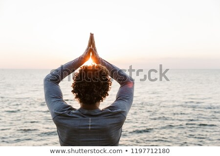 Handsome young sportsman make yoga exercises at the beach. Stock photo © deandrobot