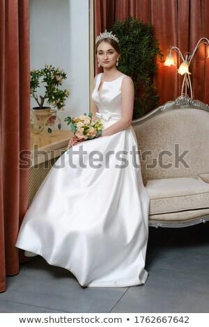 Güzel gelin oturma beyaz kanepe gelinlik Stok fotoğraf © dmitriisimakov