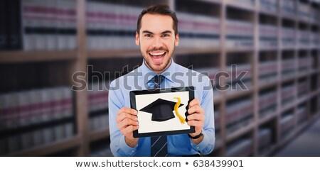 Mortar board against volumes of books on bookshelf in library Stock photo © wavebreak_media