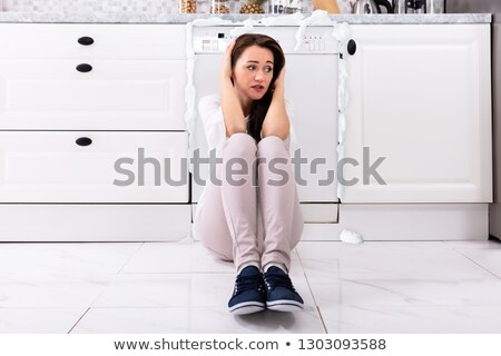 Upset Woman Sitting In Front Of Damaged Dishwasher Stock photo © AndreyPopov