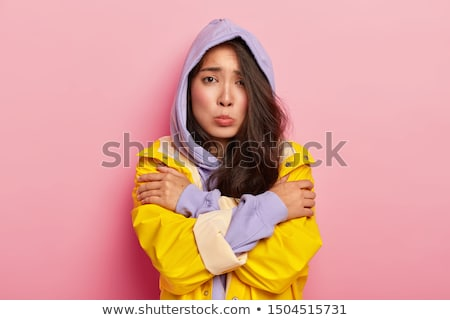 Sad young girl wearing raincoat standing Stock photo © deandrobot