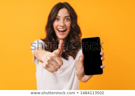 Happy cute young woman posing isolated over yellow background showing display of mobile phone. Stock photo © deandrobot