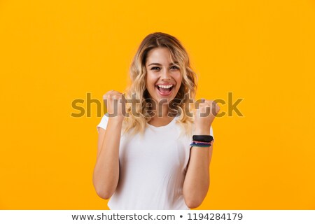 Photo of joyous woman in basic clothing screaming and clenching  Stock photo © deandrobot
