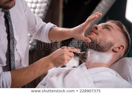 Smiling hairdresser holding razor and shaving brush Stock photo © Kzenon