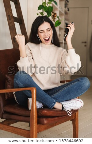 photo of excited woman 20s wearing earphones smiling and holding stock photo © deandrobot
