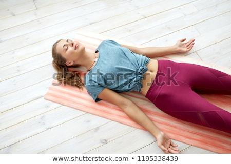 woman doing yoga corpse pose at studio Stock photo © dolgachov