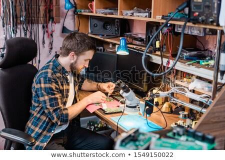 Young professional mechanic with small steel tweezers repairing demounted gadget Stock photo © pressmaster