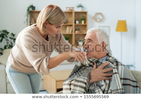 Young woman giving her sick father glass of water while taking care of him Stock photo © pressmaster
