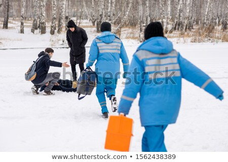 Rear view of paramedics in blue uniform hurrying to sick person lying in snow Stock photo © pressmaster