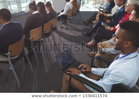 High angle view of young disabled African american businessman using laptop during seminar in office Stock photo © wavebreak_media