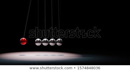 Metallic Balls Mechanism Spotlighted on Black Background Stock photo © make
