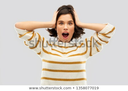 impressed woman in pullover holding to her head Stock photo © dolgachov