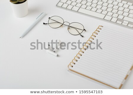 Wireless earphones, eyeglasses, pen, notebook and computer keypad on white desk Stock photo © pressmaster