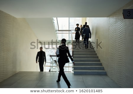 Several young intercultural people in formalwear moving upstairs and forward Stock photo © pressmaster
