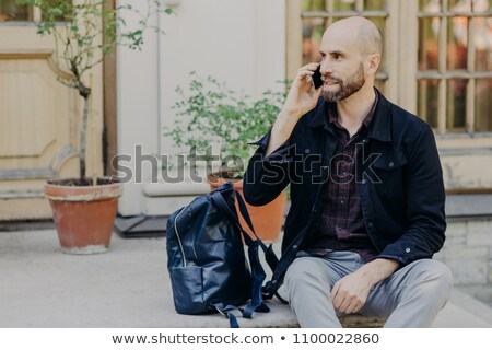 Handsome bald male with beard, has rest after long stroll outdoor, speaks via cell phone, focused as Stock photo © vkstudio