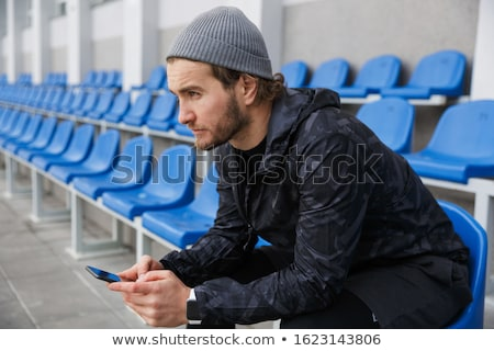 Confident young sportsman sitting on tribune seats at the stadium Stock photo © deandrobot