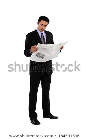 Stock photo: Businessman stood reading the newspaper