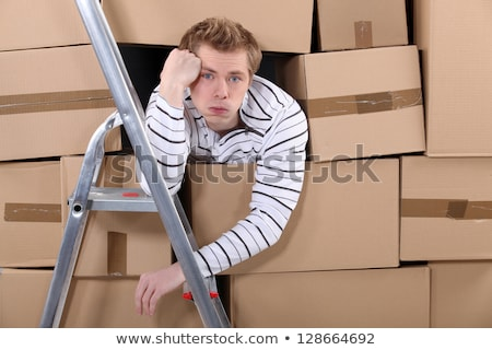 Stock photo: Man stuck behind stacks of cardboard boxes