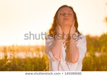 Young woman practicing yoga on the lawn near beach at sunset Stock photo © HASLOO
