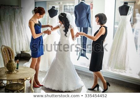 Brides at wedding dress fitting in shop Stock photo © Kzenon