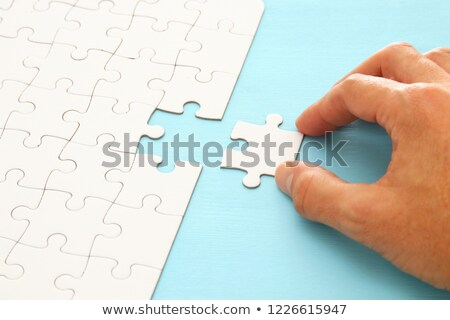 Male hand putting a missing piece into jigsaw puzzle Stock photo © stevanovicigor