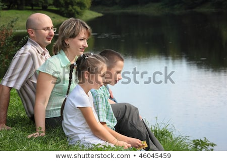 family in early fall park father mother little boy and girl is sitting near pond stock photo © paha_l