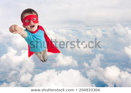 boy in red super hero cape and mask flying on air Stock photo © dolgachov
