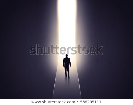 Photo stock: Business Person Looking At Wall With Light Tunnel Opening