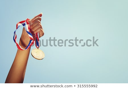 athlete with medal and hands raised stock photo © rastudio