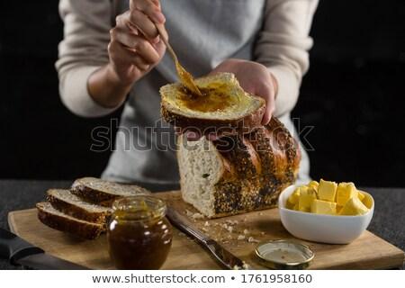 Woman applying jam over multigrain bread slice Stock photo © wavebreak_media