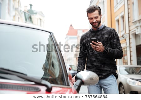 Man with his cellular phone, smiling Stock photo © IS2