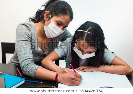 Mother helping daughter with homework Stock photo © IS2
