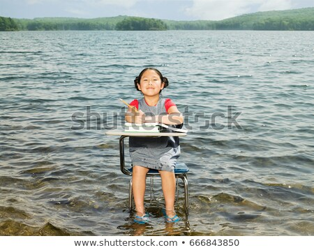 A girl sat at a desk in a lake Stock photo © IS2
