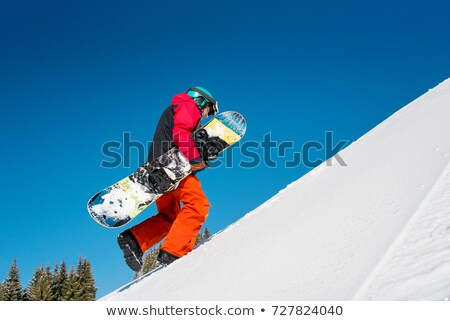 Male snowboarder walking up mountain Stock photo © IS2