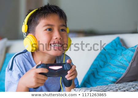 portrait of asian happy gamer boy playing video games online on stock photo © deandrobot