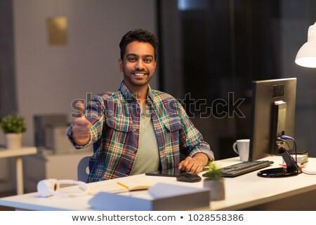 creative man showing thumbs up at night office stock photo © dolgachov