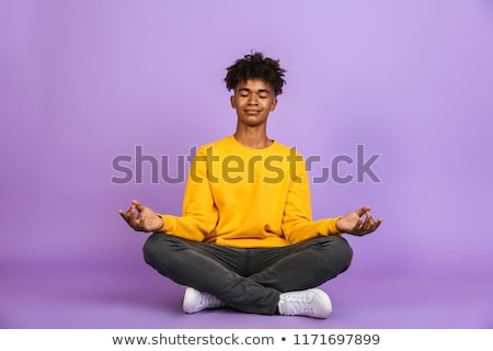 Portrait of relaxed african american boy sitting in lotus pose a Stock photo © deandrobot