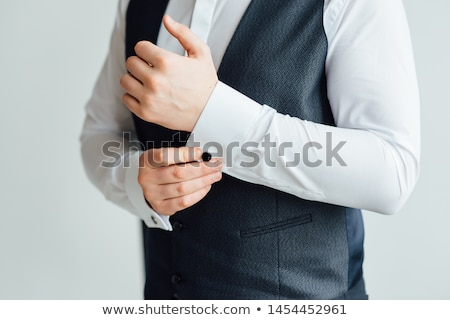 Close-up of a man in a tux fixing his vintage cufflink. groom bow tie cufflinks Stock photo © ruslanshramko