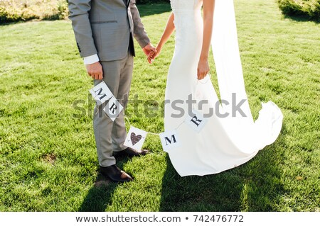 newlyweds hold hands and hold a paper garland stock photo © ruslanshramko