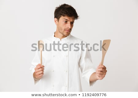 Young chef isolated over white background holding spoon and spade. Stock photo © deandrobot