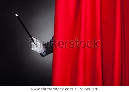 Magician's Hand Holding Magic Wand Behind Curtain Stock photo © AndreyPopov