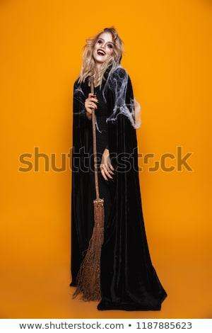 Full length image of dangerous witch woman wearing black costume Stock photo © deandrobot