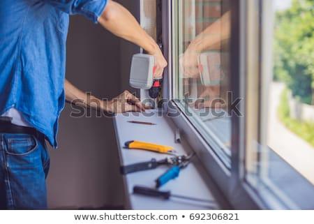 Uomo blu shirt finestra installazione costruzione Foto d'archivio © galitskaya