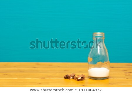 Stock photo: Glass bottle half full of milk with cookie crumbs