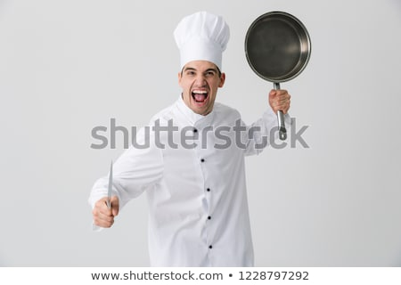 Emotional young man chef indoors isolated over white wall background holding frying pan. Stock photo © deandrobot